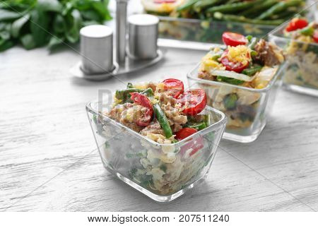 Bowls with yummy green bean casserole on wooden table