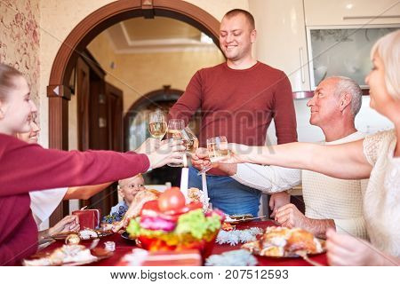 Cheerful, fantastic, big family cheers glasses of wine at the festive dinner table on a blurred background. Christmas or Thanksgiving domestic celebration.