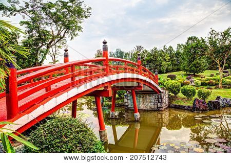 Red wooden bridge over tranquil pond at Japanese Garden a free public park within Jurong Lake Gardens in Singapore. The gardens are popular among exercise enthusiasts bird watchers and nature lovers.