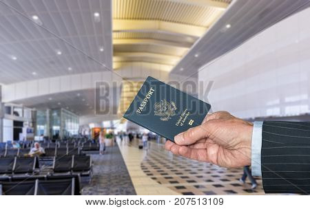 Senior caucasian businessman arm holding a USA passport to show to official in airport terminal for international flight
