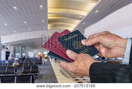 Senior caucasian businessman arm choosing to show US or EU or UK passport at immigration