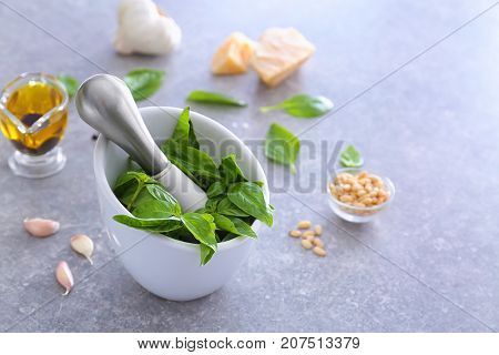 Mortar with pestle and basil leaves on table