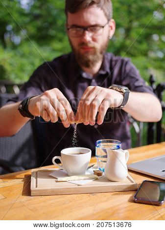 Close-up of a young man sweetening his drink in a cafe in the fresh air.