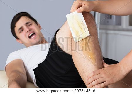 Man Screaming In Pain While Waxing Leg With Wax Strip