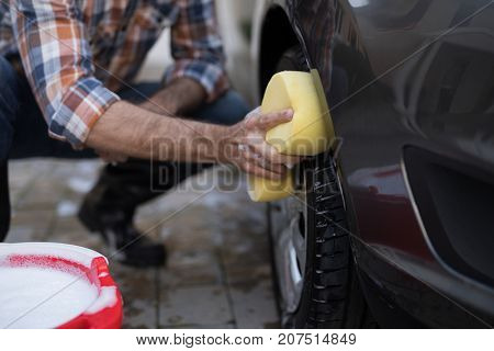 Mid-section of man washing a car on a sunny day