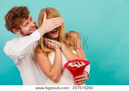 Man Giving Woman Candy Bunch Covering Her Eyes.
