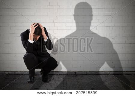 Young Businessman Getting Scared From The People Shadow Falling On Wall
