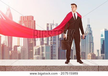 Young Superhero Businessman Standing On Surrounding Wall With City Skyscrapers Buildings In Background