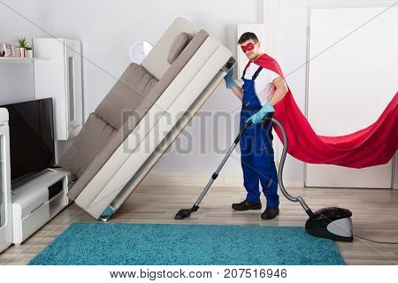 Male Janitor Wearing Superhero Costume Cleaning Wooden Floor With Vacuum Cleaner In Living Room