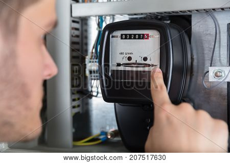 Close-up Of Young Man Pointing At Electric Meter In Fuse Box