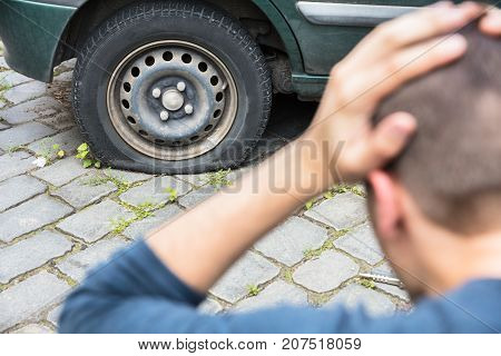Close-up Of A Worried Man With Hand On Head Looking At Punctured Car Tire
