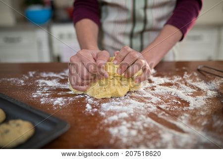 Mid section of woman kneading dough in kitchen