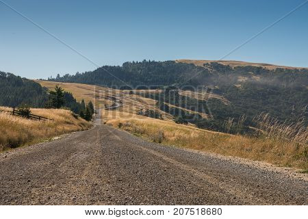 Gravel Road Snakes Through Dry Grass Hills