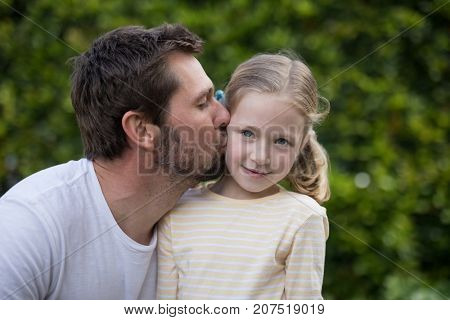 Father kissing his young girl in the park