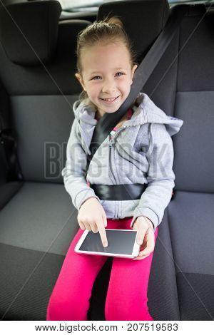 Portrait of teenage girl using digital tablet in the back seat of car