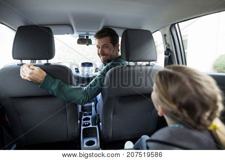 Happy teenage girl sitting in the back seat while woman driving a car