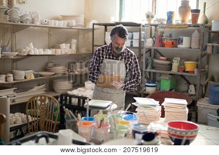 Male potter maintaining record on clipboard in pottery workshop