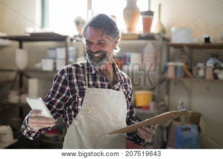 Happy potter using mobile phone in pottery workshop