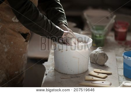 Mid section of male potter washing hands in bucket