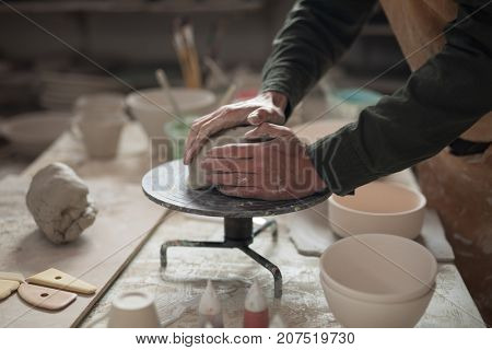 Mid section of male potter molding a clay in pottery workshop