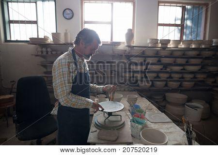Male potter molding a clay on pottery wheel in workshop