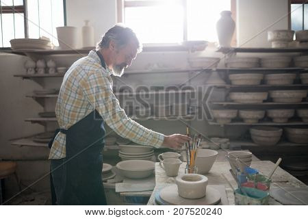 Male potter holding paint brush in pottery workshop