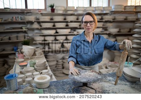 Female potter standing at worktop in pottery workshop