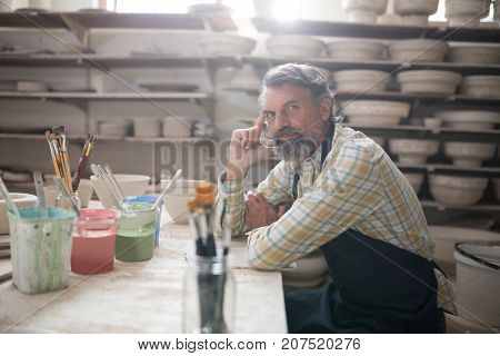 Portrait of male potter sitting at worktop in pottery workshop