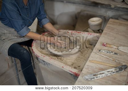 Mid section of female potter molding clay in pottery workshop