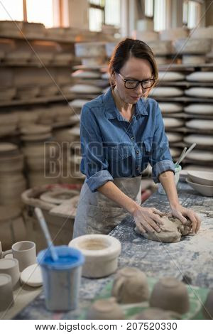 Female potter molding a clay in pottery shop