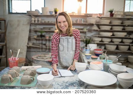 Portrait of female potter checking the orders in notebook