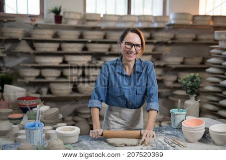 Portrait of female potter flattening the clay with rolling pin in workshop