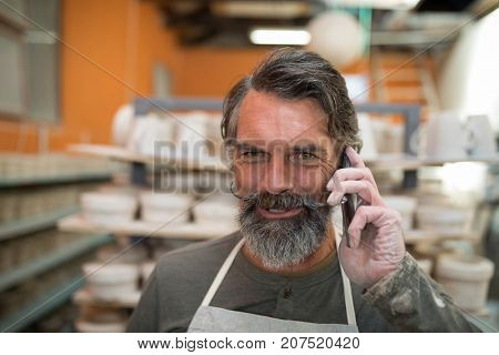 Male potter talking on mobile phone in pottery shop