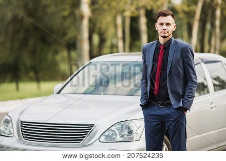 Successful businessman in a dark business suit on the background car. Stylish businessman near the car. Buy a new car. Car driver. Luxury gray car