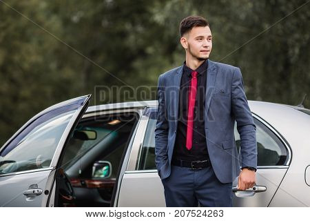 Successful luxury businessman in a dark luxury business suit with a red tie on the background of a gray luxury car. Stylish luxury man