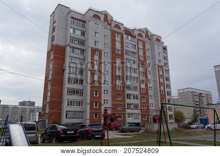 Yoshkar-Ola, Russia - October 5, 2017 Photo of a multi-storey brick house made of white and red brick, built in the 1990s in Yoshkar-Ola, Russia