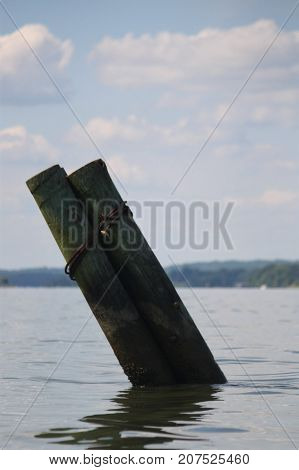 Two large wooden poles tied together in the water.