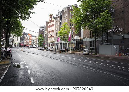 AMSTERDAM NETHERLANDS - JUNE 21 2016: Picture of the Nieuwezijds Voorburgwal Street in downtown of Amsterdam with a hotel and parked cars in a rainy day. Amsterdam Netherlands.