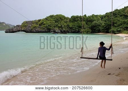 Asian girl sitting on the cradle on the beach in Thailand.