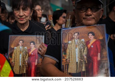 BANGKOK THAILAND - OCTOBER52017 : thai mourners people wearing black clothes and carrying king and queen of rama ix bhumibol photograph on last day of respect to their beloved king at grand palace