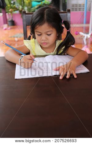 Asian child girl use Pencil write letters on the book in concept of education and learning.