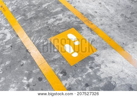 Walkway Lane In Parking Building. Painted Yellow Footsteps Between Parallel Yellow Lines On Abstract
