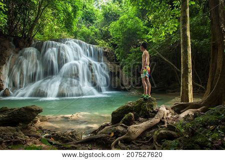 Rear View Of Young Man Standing In Front Of Waterfall/waterfall In Forest At Erawan Waterfall Nation