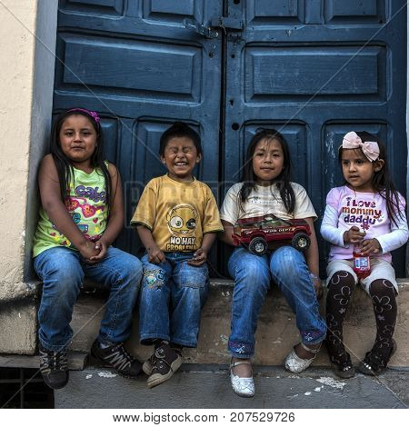 Quito Ecuador - May 27 2012: Happy Indigenous children sitting on the doorstep of a house in the historic center of Quito and smiling at the camera