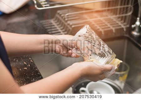 A Woman Washing Glass By Dish Soap
