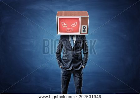 A businessman stands with hands in his pockets and wears a TV box on his head with a red screen showing an angry face. Business and success. Proactive approach. Fight off your competition.