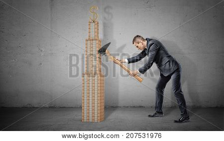 A businessman with a broken hammer fails to break a small business skyscraper with a golden dollar sign on its top. Insured business. Protection from competitors. Solid business venture.