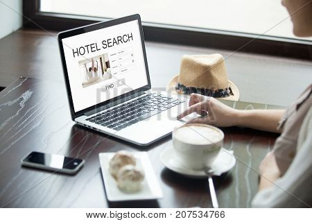 Casual woman in cafe searches for hotel on laptop, planning vacation online. Tourist using search engine to find accommodation during trip. Finding best offer for apartment, hotel or motel. Side view.