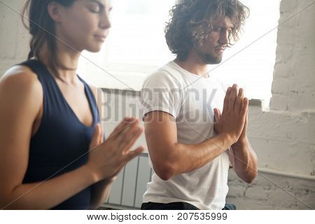 Group of young sporty people making namaste gesture, man and woman meditating, practicing yoga lesson with instructor, working out, indoor close up image, studio. Wellbeing and wellness concept