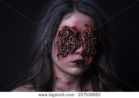 Girl with realistic sores and worms in her eyes. Creative halloween makeup.